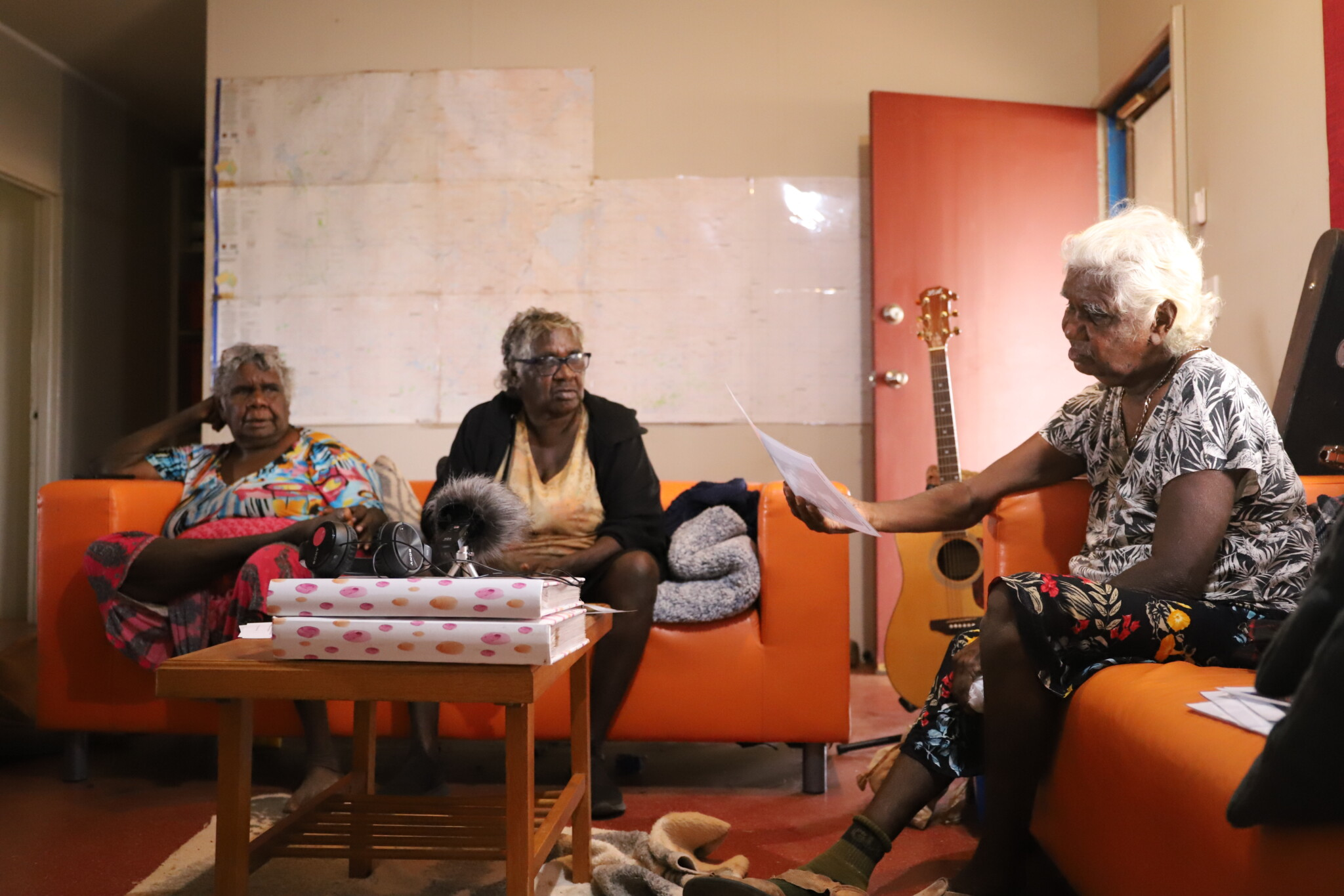 Three indigenous women sit on couches, sharing stories and photos with each other