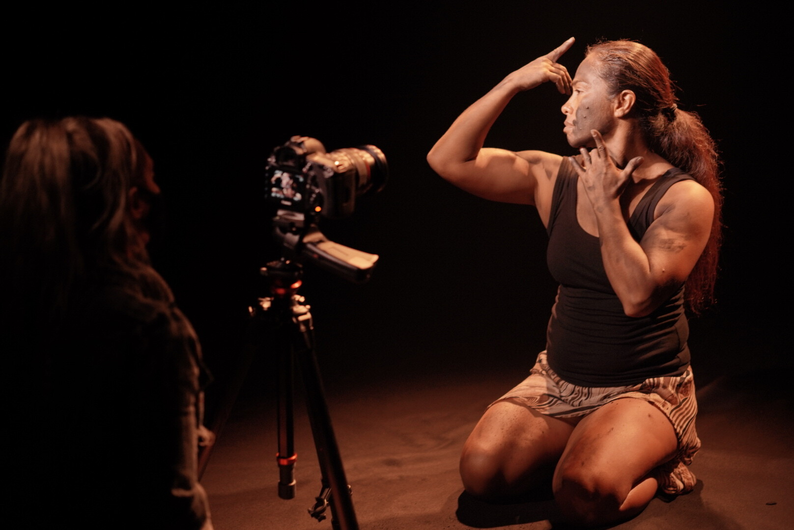 An indigenous woman performs a dance routine on her knees, framing her face with her hands, while being filmed