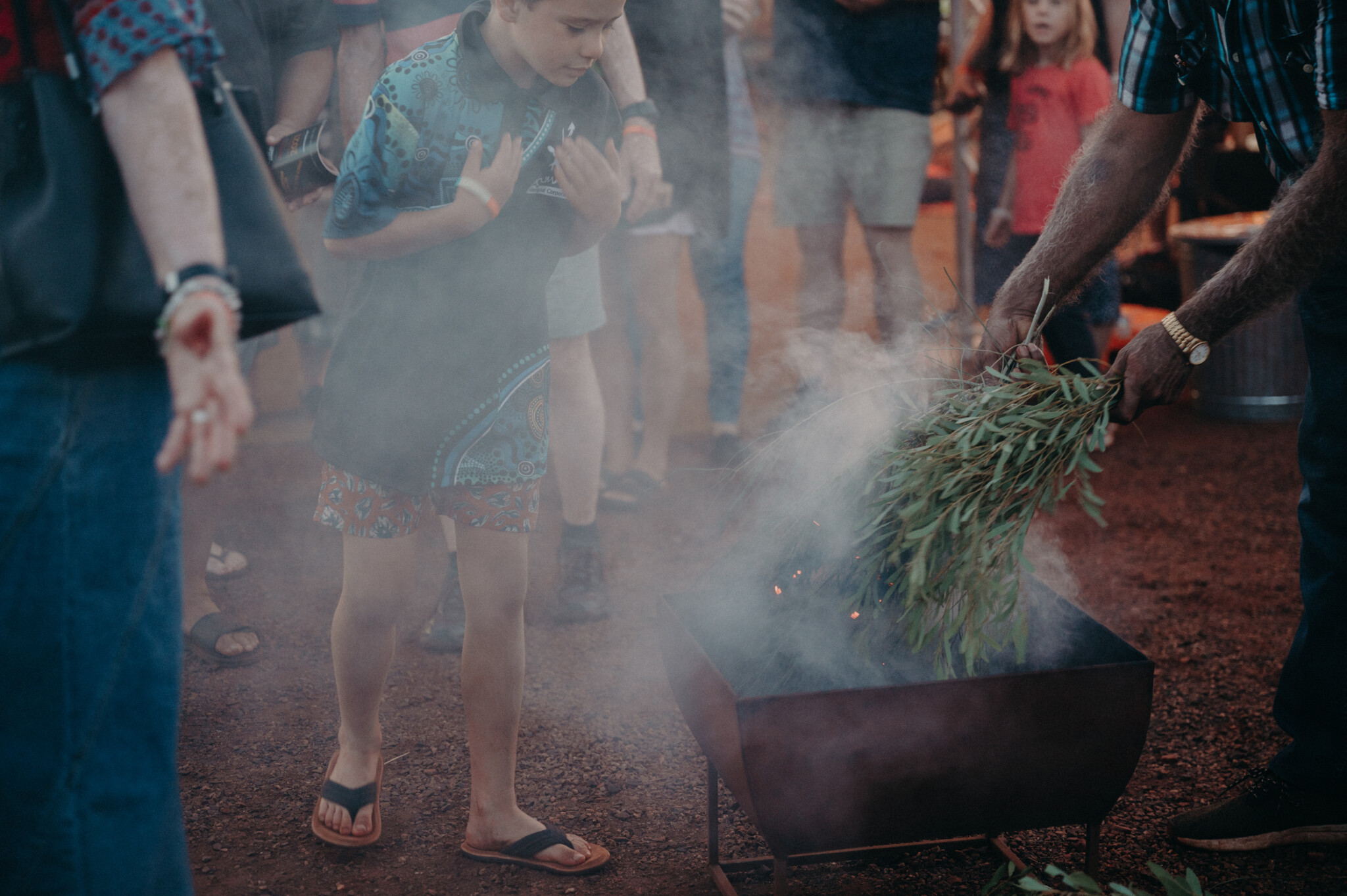 A young boy approaches the smoking ceremony, the area is filled with smoke from smouldering native plants