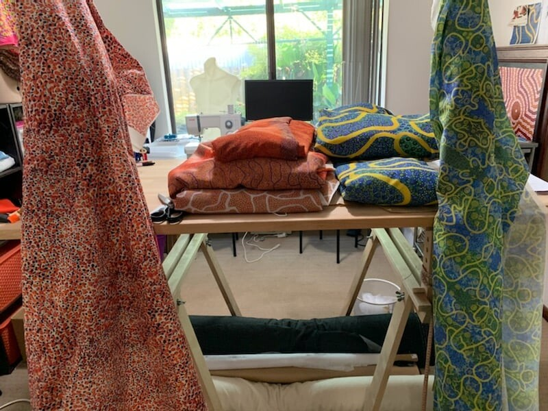 Stacks of fabric with patterns from Bianca's paintings inside a store