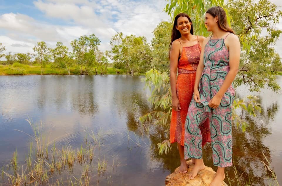 Two girls stand by a river, smiling as they model the Jaru Girl fashion line