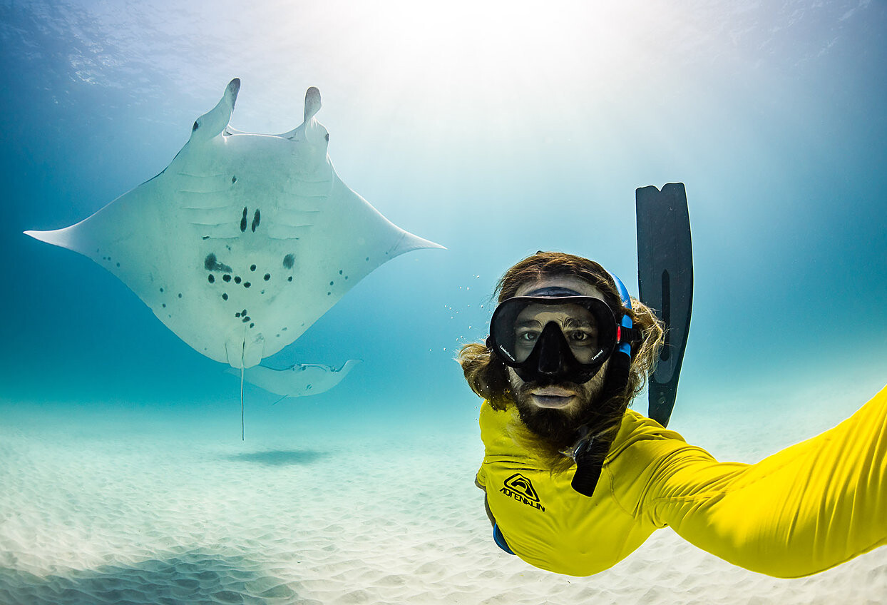 Jess posing for a selfie underwater with a manta ray.