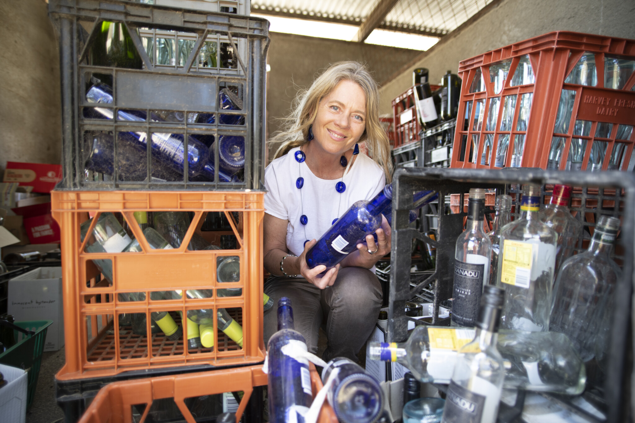 Cindy holding an empty bottle, surrounded by crates of empty bottles.