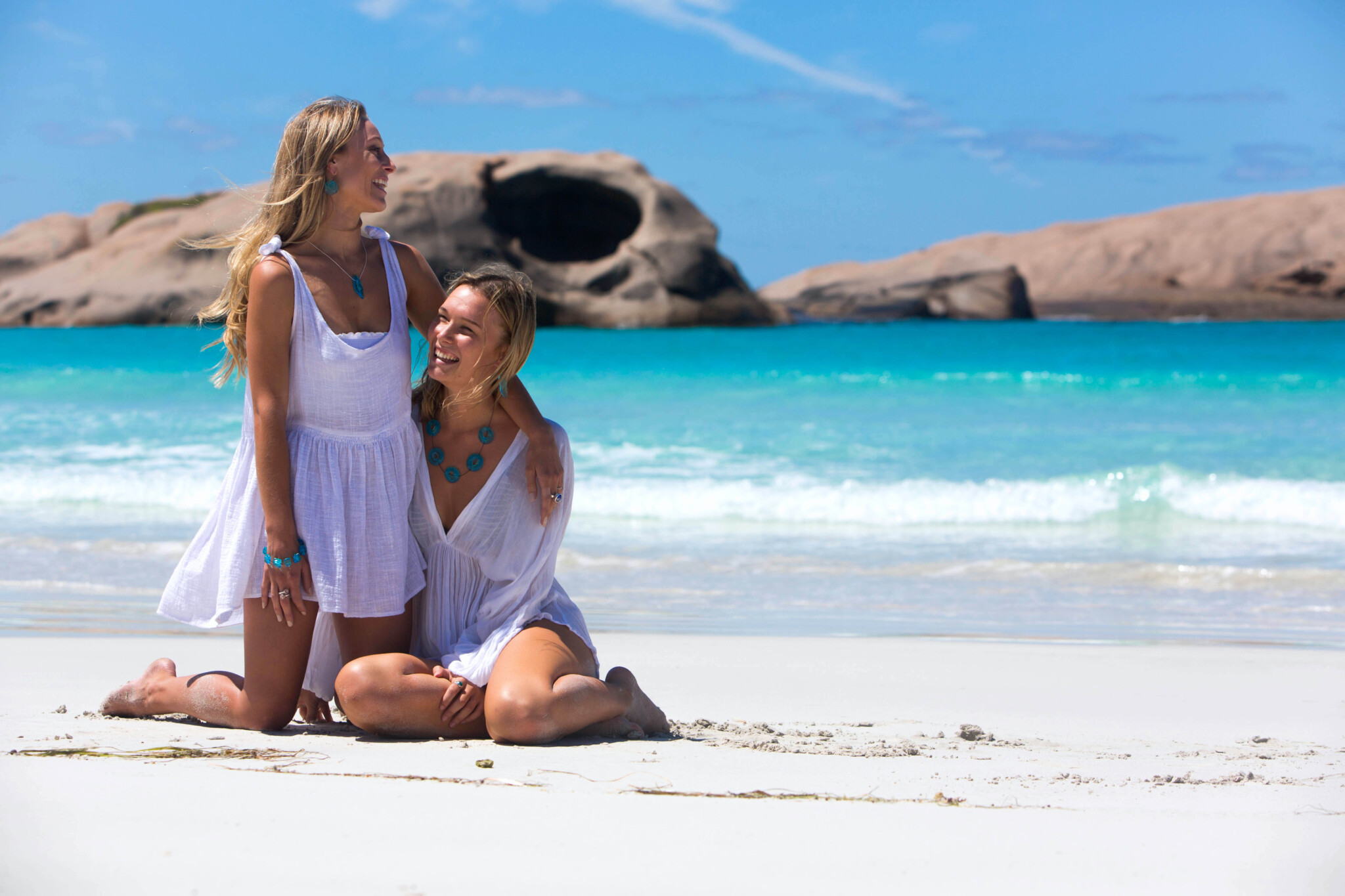 Two models sitting on the sand at the beach