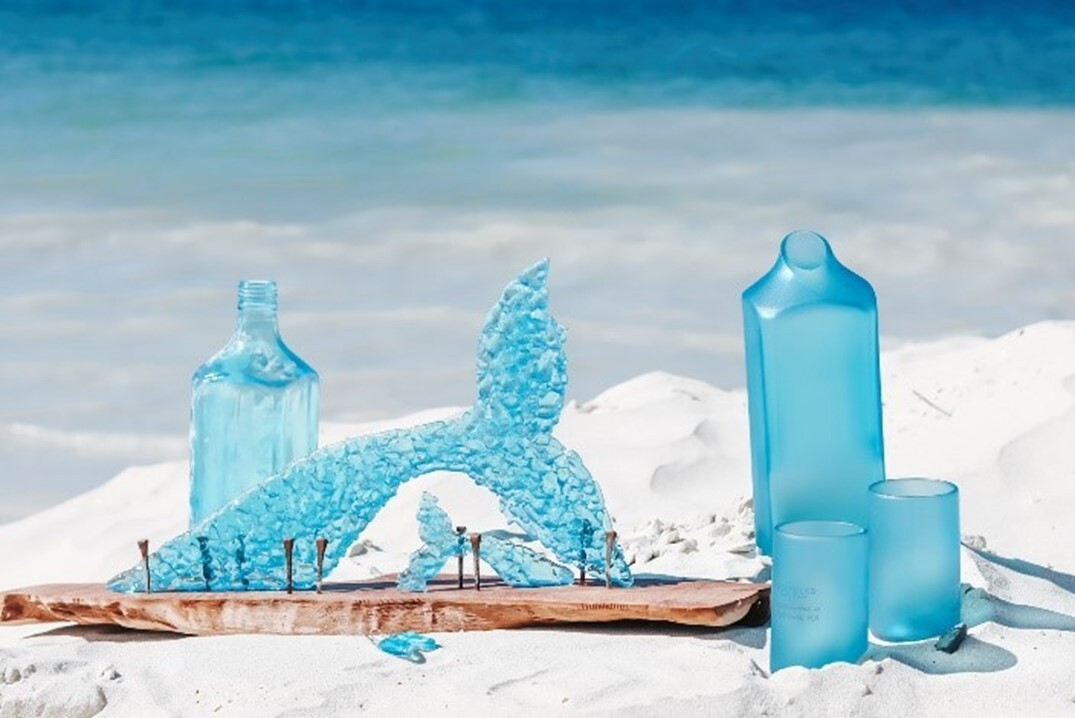 Bright blue carafe, glasswear, bottle, and whale scultpure on the sands of the beach