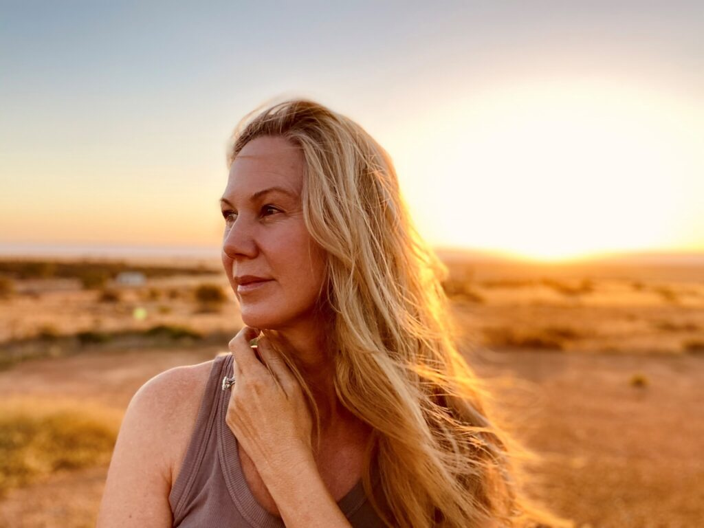 Lynda Howitt standing in a desolate field. Lynda has long blonde hair and is wearing a purple singlet. She is looking into the distance and her left arm is crossed over so her hand sits under her chin. The image is backlit and golden, and the background is out of focus.