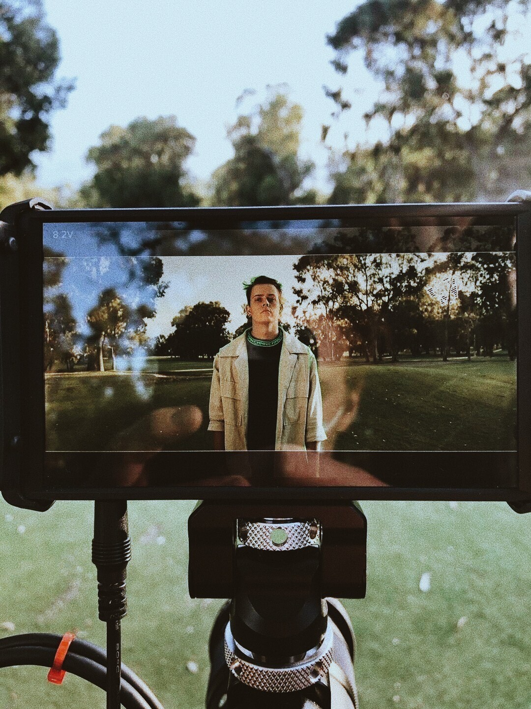 Photo of camera LCD screen showing a still of JOSHUA in a green field.