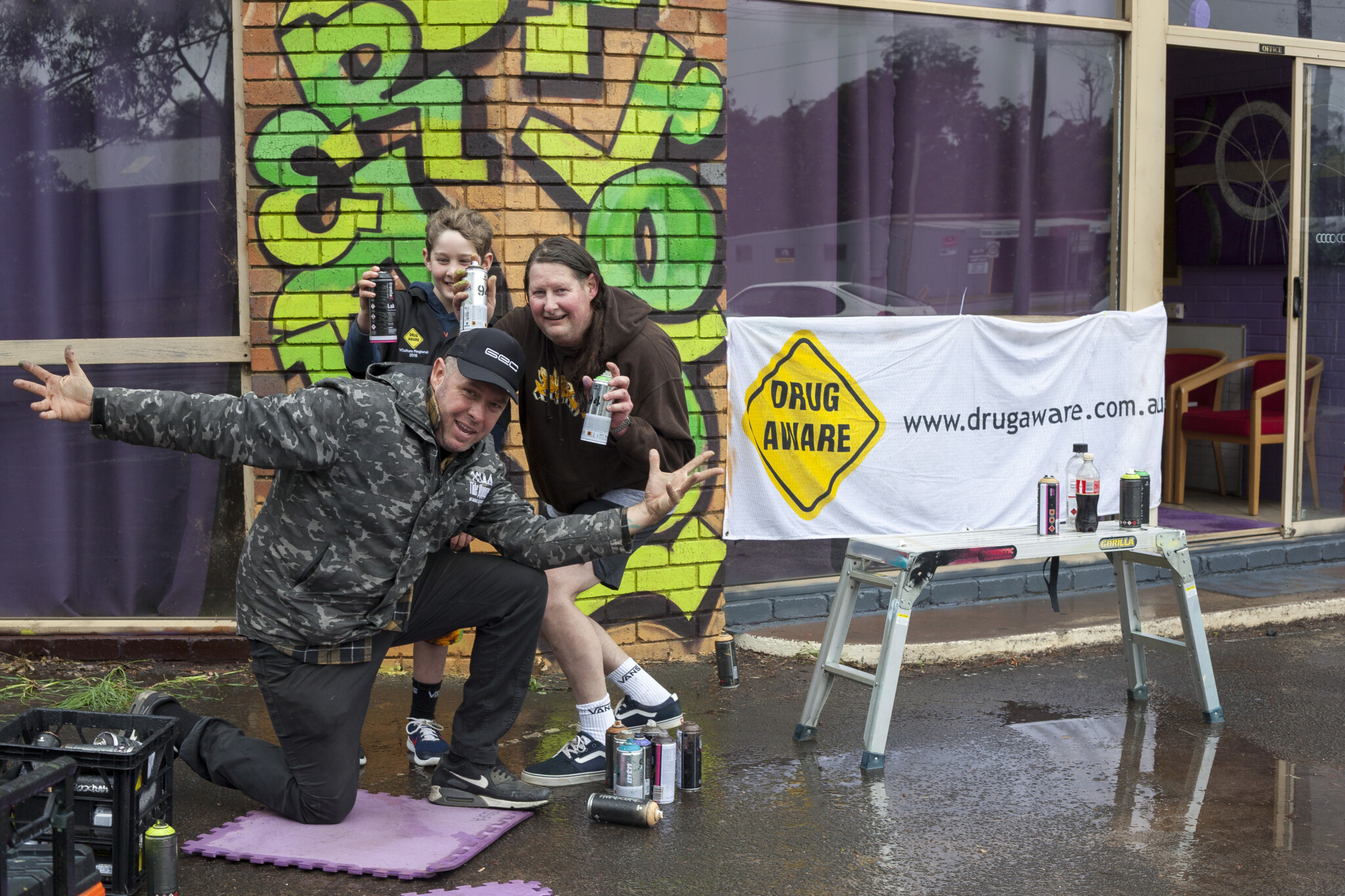 A young boy and an older man hold spray cans while a man poses on his knees with arms outstretched in front of graffiti mural.
