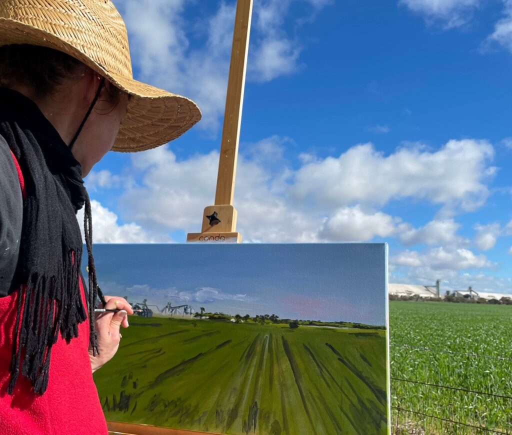 Artist Siobhan Kelley working on a plein air painting of a wheat field and blue sky. Siobhan is in the foreground and is wearing a black and red jumper and straw hat while she paints a canvas on an easel.