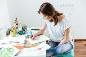 Happy attractive woman artist making sketches in workshop