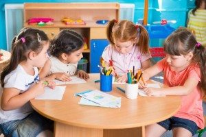 Group of little prescool girls drawing with colorful pencils