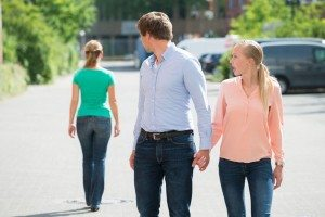 man holding his grifriends hand and looking at another woman