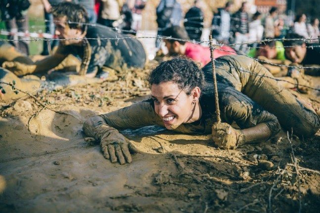 Woman crawling under a barbed wire in a race (Farinto).