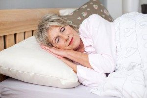 Senior woman smiling while sleeping in bed
