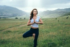 Young woman practicing yoga outdoor in the nature