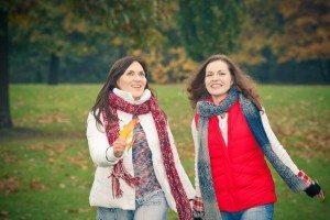 two women walking through a park
