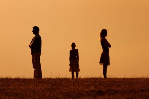 Silhouette of a angry husband and wife on each other with their daughter standing in the middle.
