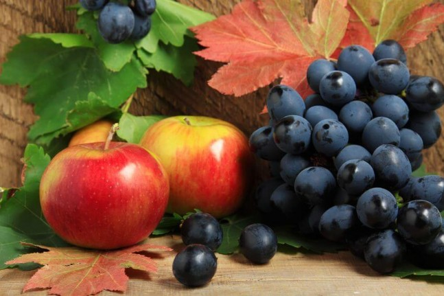 ripe apples and bunch of grapes on wood