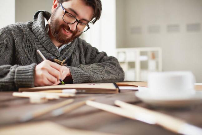 happy man drawing at his desk