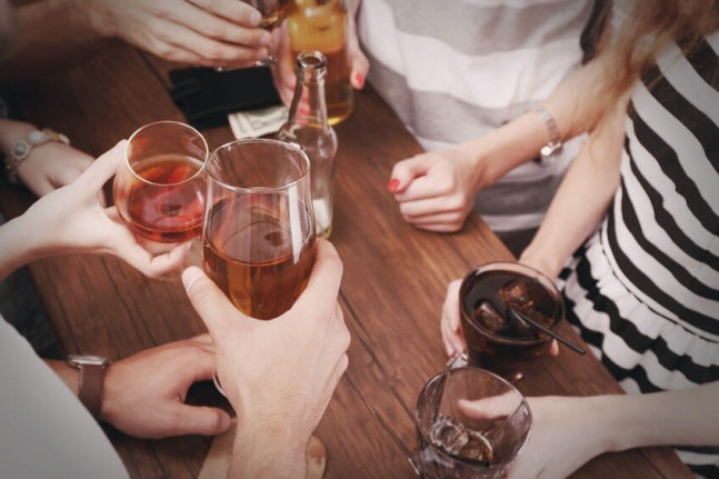 top view of hands holding alcoholic drinks at a bar