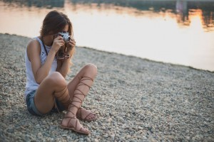 Girl sitting on the beach and photographing
