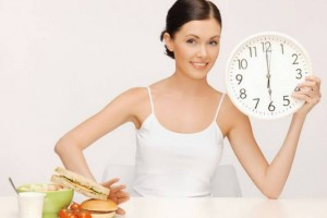 picture of woman with big clock pushing food away