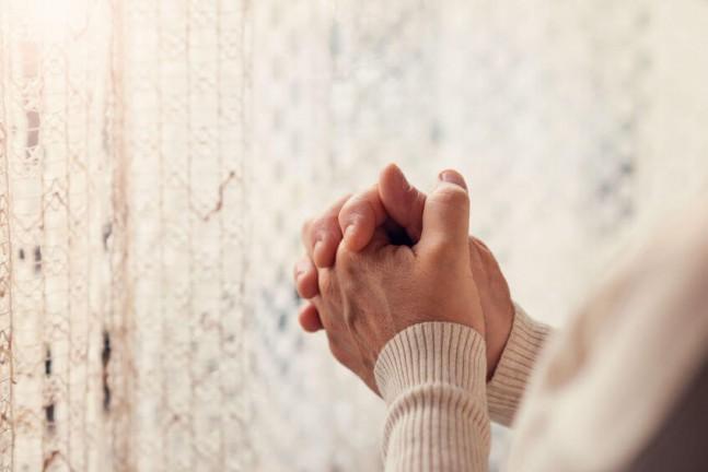 hands praying near a curtain windows