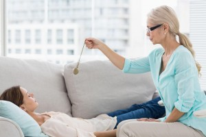 Hypnotherapist holding pendulum by patient on sofa at home