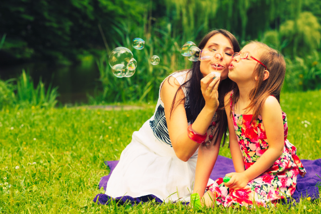 mother and little girl daughter child blowing soap bubbles outdoor. parent and kid having fun in park. happy and carefree childhood. good family relations.
