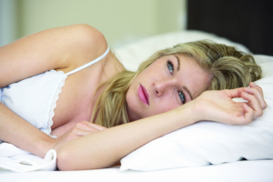 Worried Looking Young Woman On Bed