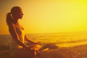 woman on the beach practising meditation