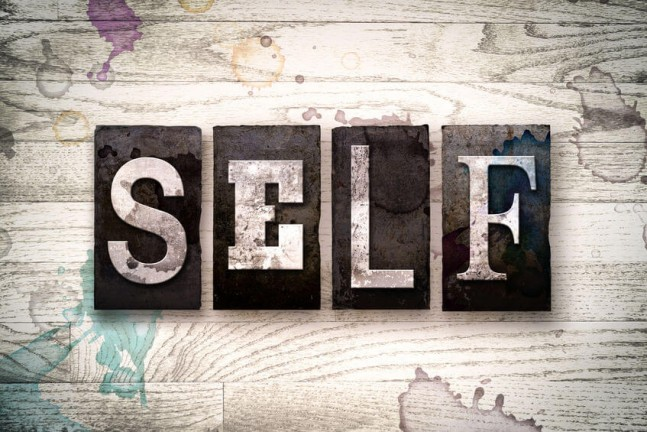 "The word ""SELF"" written in vintage dirty metal letterpress type on a whitewashed wooden background with ink and paint stains."