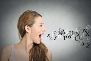 Side view portrait woman talking with alphabet letters coming out of her open mouth