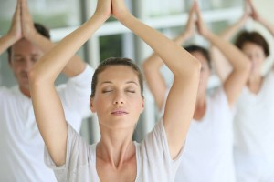 woman performing yoga in a class with eyes closed