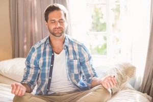 Handsome man practising meditation on his bed at home in bedroom
