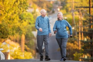 elderly couple walking for exercise with weights