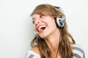 Beautiful young brunette listening to music with headphones, laughing