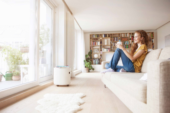 Smiling woman at home sitting on couch looking out of window