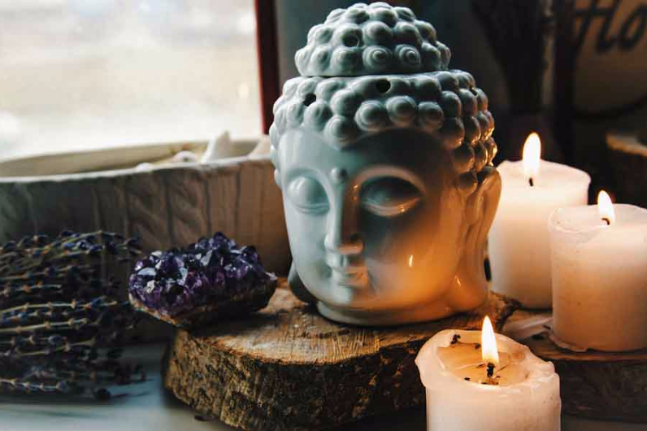 spiritual ritual meditating face of Buddha ametist candles on old wooden background Esoteric tonal curves color