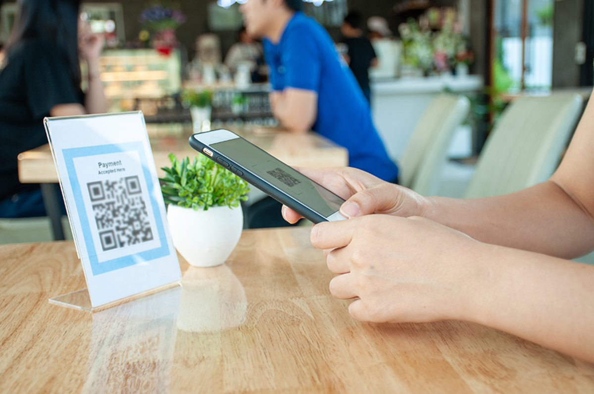 Women are using mobile phones scan qr code get food discounts pay food through stores