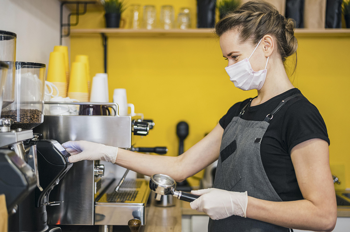 Side view female barista with latex gloves preparing coffee machine