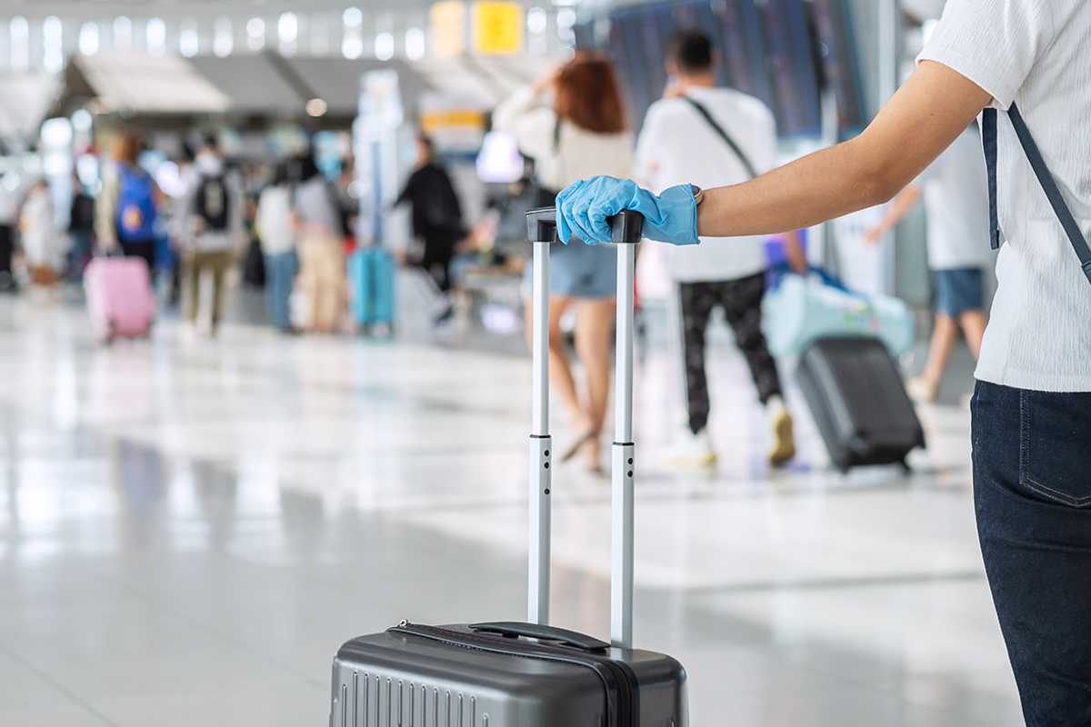 Young woman traveler wearing nitrile glove holding handle luggage airport terminal