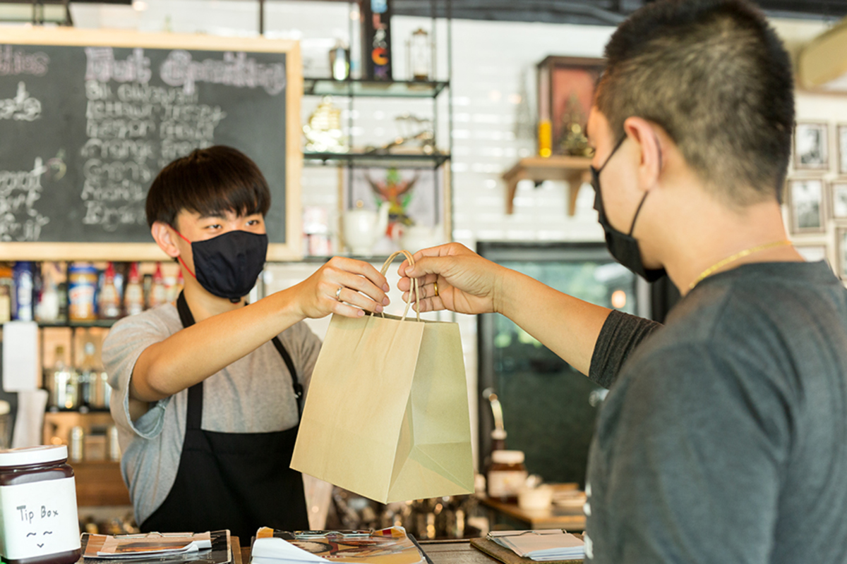 Social distance conceptual waiter giving takeaway bag customer cafe