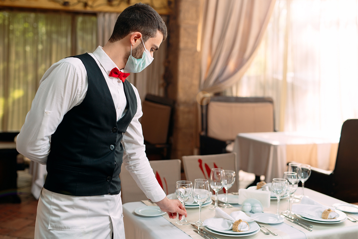 Waiter wearing medical protective mask serves table restaurant