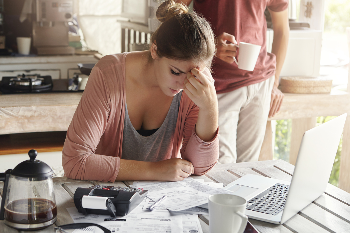 Thoughtful stressed young female sitting kitchen table with papers laptop computer trying work through pile bills frustrated by amount domestic expenses while doing family budget