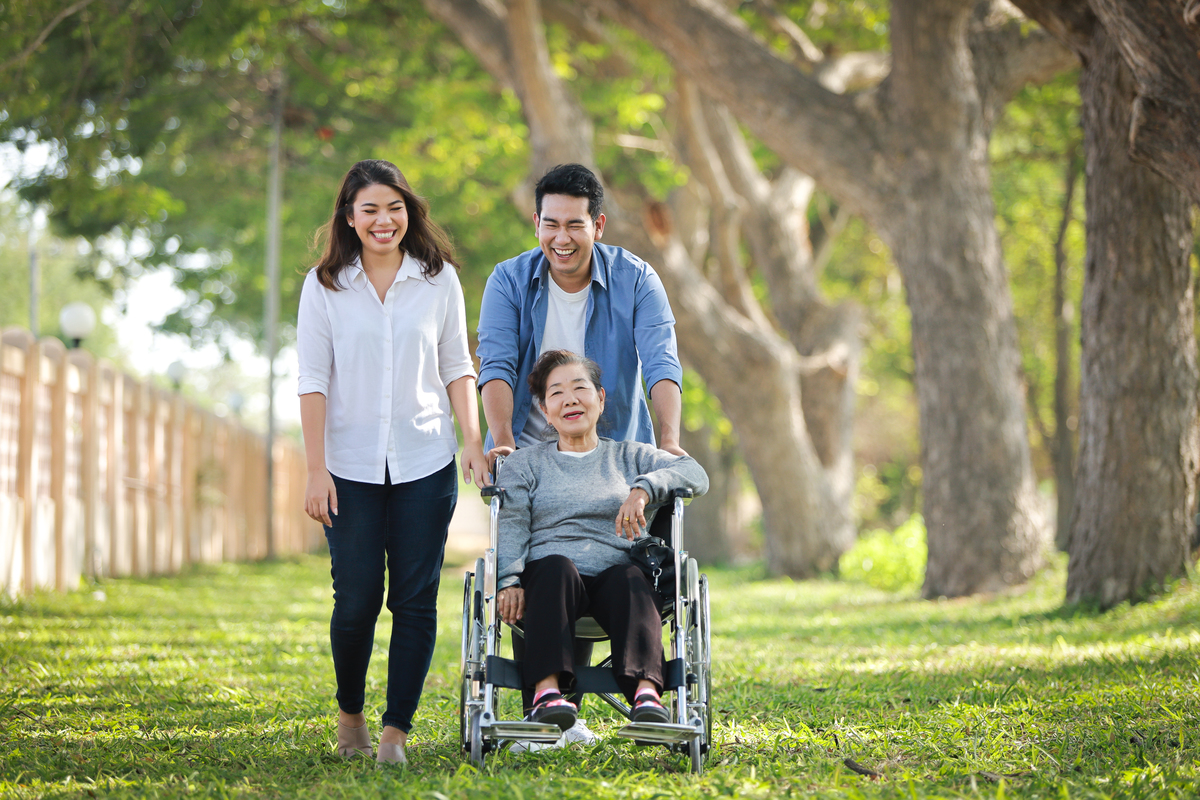 Asian senior woman sitting wheelchair with family happy smile face green park
