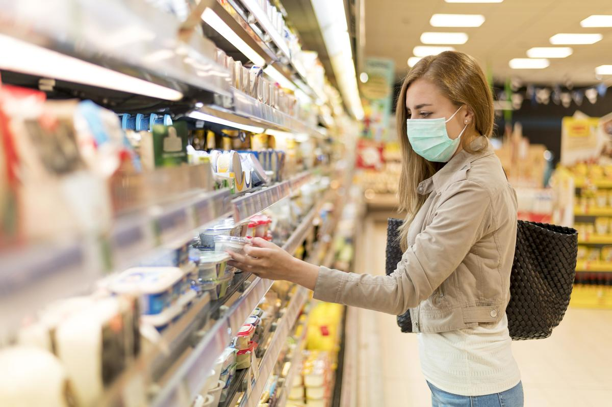 Side view woman with mask grocery shopping