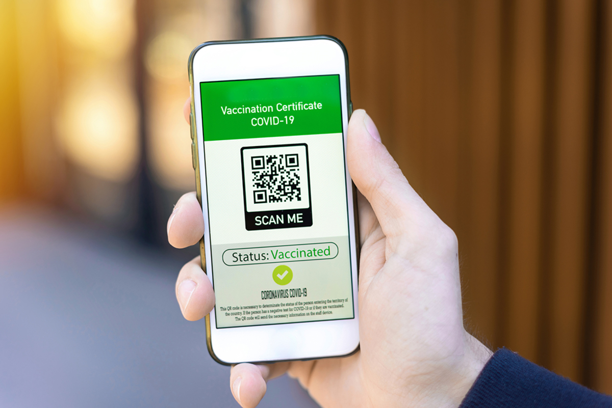 Male hand holding smartphone with international vaccination certificate covid 19 qr code