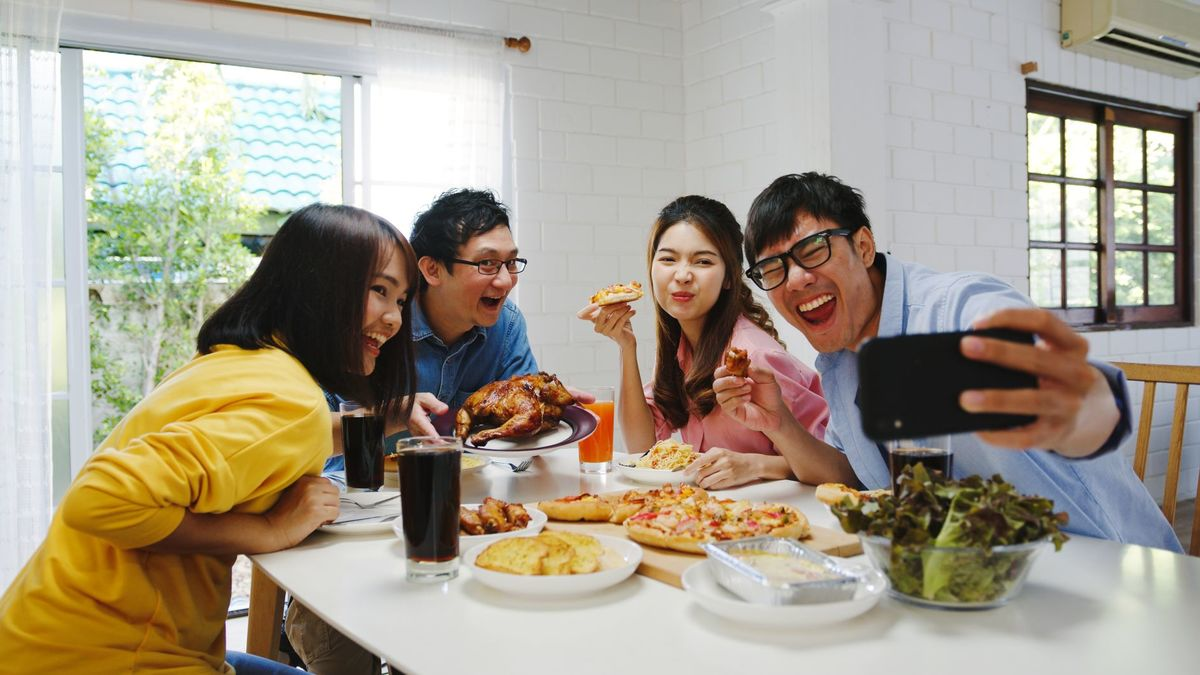 Happy young group having lunch home asia family party eating pizza food making selfie with her friends birthday party dining table together house celebration holiday togetherness