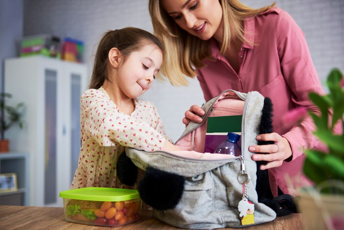 Young mum daughter packing backpack school